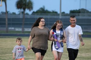 Senior Cheerleader Maria Wunder walks with her family.