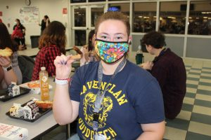 Female student sits at the lunch table wearing ID badge and mask.