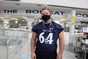Student stands in the lunchroom wearing a mask, ID badge, and football jersey.