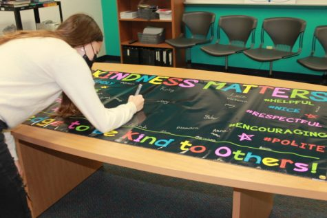 A girl is signing a colorful banner