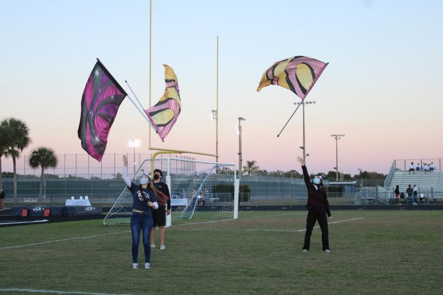 3 members of the color guard are practicing with brightly colored flags in the football field