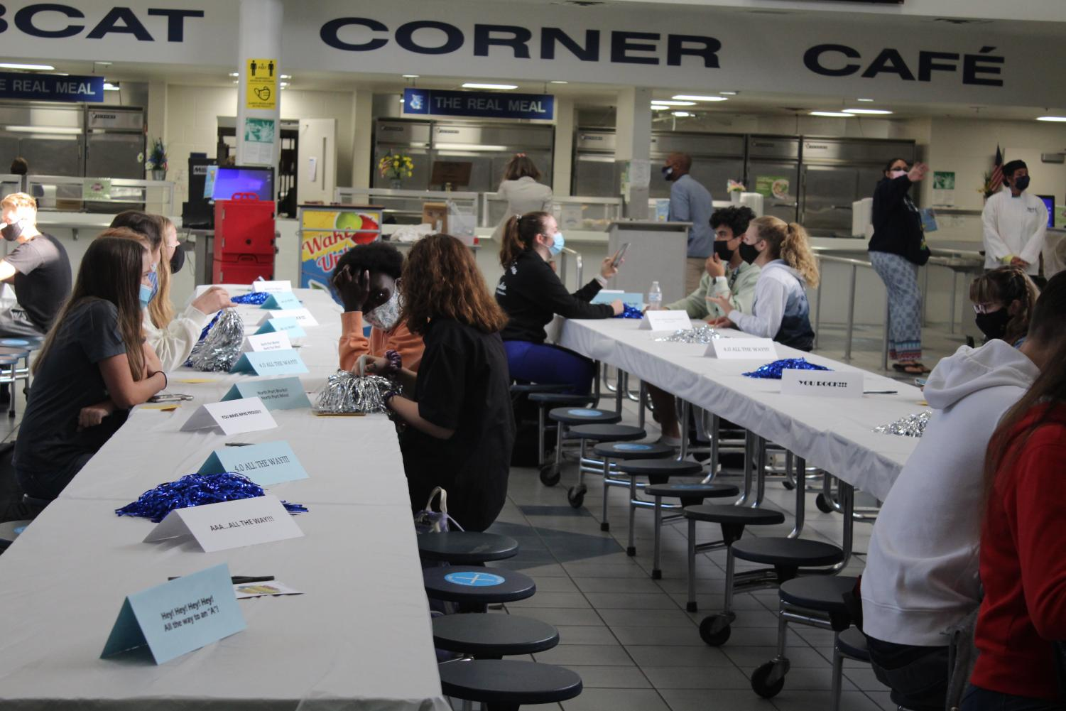 students sit at the cafeteria tables and eat breakfast