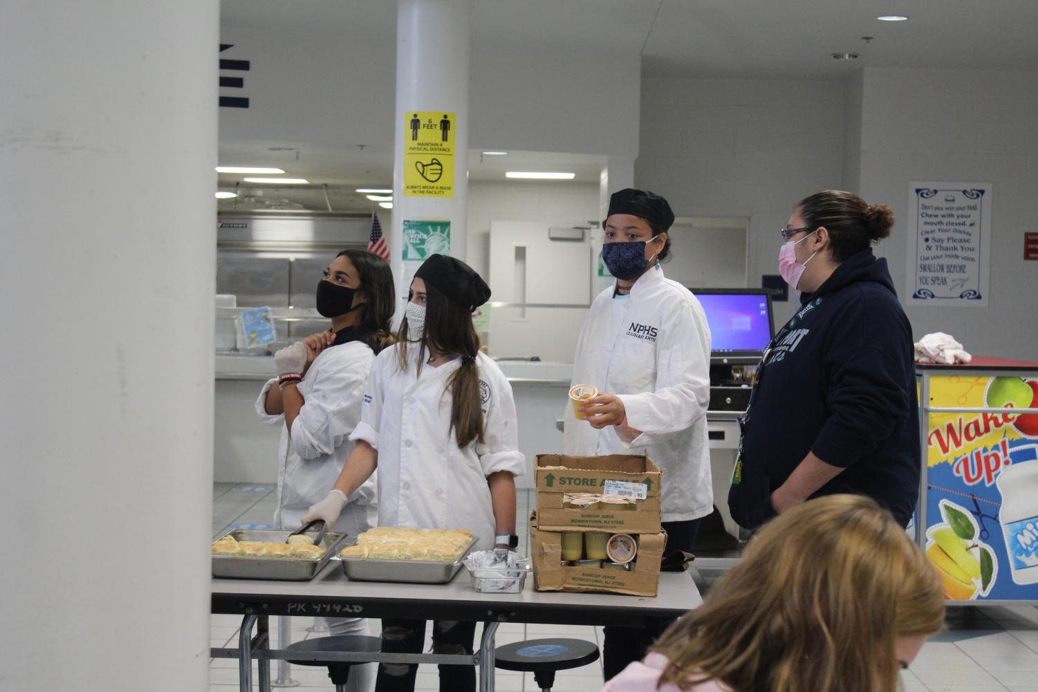 culinary students in white coats serve breakfast in the cafeteria