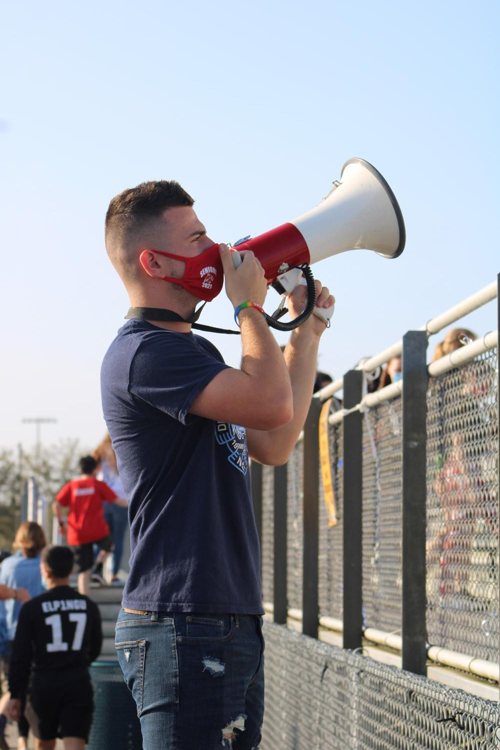 Logan King speaks through a megaphone while wearing his mask.