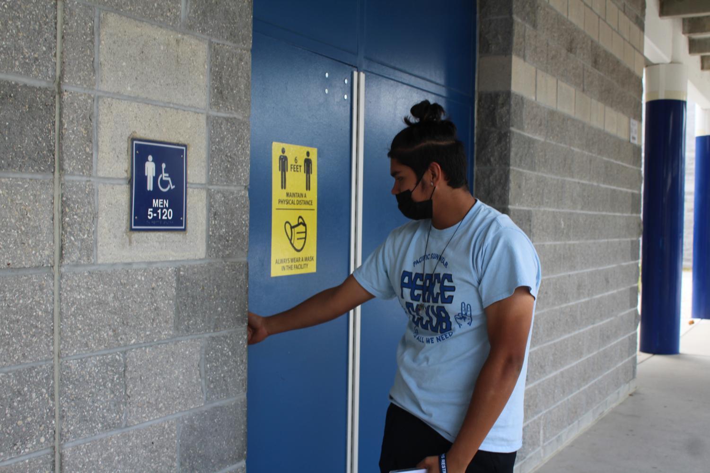 Male student holding door on his way into bathroom.