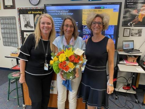 Dr. Jennings, Ms. Fusco, and Mrs. King posing while Mrs. King is holding flowers.