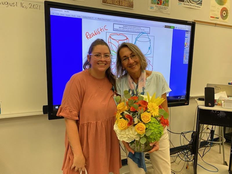 Mrs. King is holding flowers standing next to Mrs. DuBois